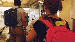 Bangkok, Tajlandia 22 2015 Listopad, pasażery z plecakami na travelator w lotnisku międzynarodowym telefon kobieta Obrazy Royalty Free