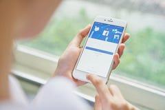 Bangkok Tajlandia, Sierpień, - 23, 2017: ręka naciska Facebook ekran na jabłku iphone6, Ogólnospołeczni środki używa dla informat Obrazy Stock