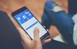 Bangkok Tajlandia, Sierpień, - 23, 2017: ręka naciska Facebook ekran na jabłku iphone6, Ogólnospołeczni środki używa dla informat Zdjęcie Stock