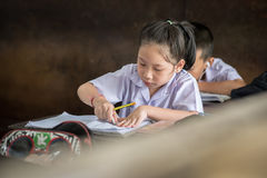 BANGKOK TAJLANDIA, Sierpień 23 -, 2017: Studencka dziewczyna studiuje bardzo koncentrat Robi pracie domowej w sala lekcyjnej przy Fotografia Royalty Free
