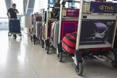 Bangkok, Thaïlande - 28 juin 2015 : Les chariots empilés ont chargé avec des bagages contre le passager masculin poussant le char Images stock