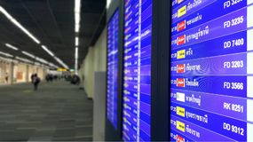 Bangkok, Thaïlande - 31 mars 2016 : Horaire de vol avec le fond de passagers de ligne aérienne de tache floue à l'aéroport d'intr Photographie stock libre de droits