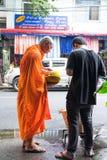 BANGKOK, THAÏLANDE - 28 SEPTEMBRE 2016 : Un aliment de offre d'homme à un moine Images stock