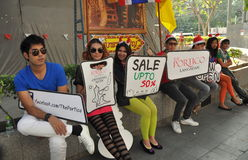 Bangkok, Thailad: People Advertising a New Store. Young employees at the new Portico shop sitting on Sukhamvit Road in Bangkok, Thailand holding advertising Royalty Free Stock Photos