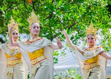 Thai traditional dance with beautiful woman on golden cultural costume performing on the stage for Songkran festival. BANGKOK, THAILAND. – On April 15, 2018 stock photo