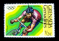 A stamp printed in Grenada shows an image of a man cycling on road bike for 1976 Olympic games Montreal Canada. stock image