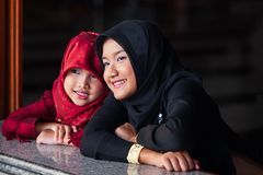 Couple adorable muslim girl in traditional clothing, black and red hijab or niqab and abaya smiling and watching out the window. stock photo