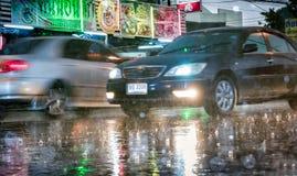 BANGKOK THAILAND - APRIL 27: Billyktor på en registreringsThailand saktar rörande bilorsaker att glo i hällregn, som den kör ner royaltyfri fotografi