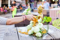 Hand pouring water to gold buddha with white lotus on Songkran Festival. Bangkok, Thailand - April 13, 2017 :  Hand pouring water to gold buddha with white Royalty Free Stock Images