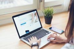 Bangkok Thailand - April 19, 2018: kvinnabruksbärbar dator på de Paypal för tabellvisningskärm webbsidorna Arkivfoton