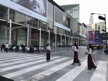 BANGKOK THAILAND - APRIL 16, 2018: Kvinnor i religiösa dräkter med annonsen för iPhone X i bakgrunden royaltyfria foton