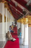 Bangkok Thailand - April 29, 2014 Man bredvid en grupp människor som vilar på Wat Phra Kaew, tempel av Emerald Buddha arkivbilder