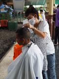 A hairdresser cuts the hair of a traveller at Bangkok railway station Royalty Free Stock Photos
