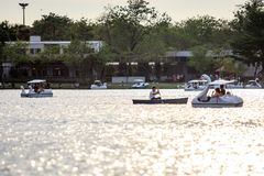 People ride duck boat at public park name Suan Luang Rama IX on sunset time Bangkok, Thailan. Bangkok, Thailand. - April 16, 2017 : People ride duck boat at royalty free stock photos
