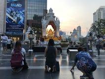 BANGKOK, THAILAND - 16. APRIL 2018: Religiöse Leute beten nahe buddist Schrein im Stadtzentrum mit Wolkenkratzern in lizenzfreies stockbild