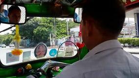 Tuk tuk ride in Bangkok. BANGKOK, THAILAND - APRIL 22, 2018: A tuk-tuk driver drives his iconic vehicle through a street in Pathum Wan district on April 22, 2018 stock footage