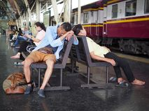 Two men sleep on a bench at Bangkok railway station stock photography