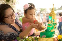 Mother and daughter sprinkling scented water on the Buddha Image in Songkran Festival. BANGKOK,THAILAND- APRIL 12,2015 : Unidentified Mother and daughter Royalty Free Stock Image