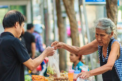 Bangkok, Thailand - April 23, 2017: Unidentified old woman street vendor is selling fried meat balls to her customer. royalty free stock photo
