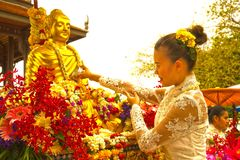 Woman sprinkling scented water on the Buddha Image in Songkran festival. BANGKOK,THAILAND- APRIL 12,2015 : Unidentified pretty Thai female sprinkling scented Stock Images