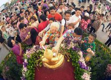 Crowd sprinkling scented water on the Buddha Image in Songkran festival. BANGKOK,THAILAND- APRIL 12,2015 : Unidentified Thai crowd sprinkling scented water on Royalty Free Stock Photos