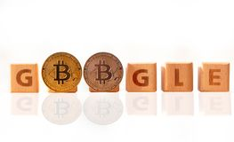 Bangkok, Thailand - April 22, 2019 : Wood word Google and two Cryptocurrency bitcoin on white background.  Google and bitcoin. stock image