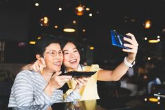 Bangkok, Thailand - Aug 28, 2018: Asian mother and daughter taking selfie, using S-Pen remote shutter on Samsung Galaxy Note 9 stock photography