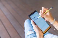 Bangkok, Thailand - Aug 28, 2018: Asian woman hand using yellow S Pen stylus on Samsung Galaxy Note 9 screen, writing reminder stock photo