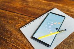 Bangkok, Thailand - Aug 30, 2018: Samsung Galaxy Note 9 with yellow S pen stylus on a notebook. Screen display note app shortcut stock photos