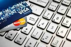 Bangkok, Thailand - August 24, 2017: Close up shot of 2 credit cards VISA and Mastercard on laptop computer with enter button focu Royalty Free Stock Photos