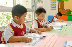 BANGKOK , THAILAND - August 23, 2017 : little boy at the desk is. Reading in classroom Royalty Free Stock Photos