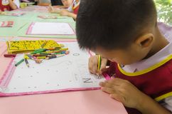 BANGKOK , THAILAND - August 23, 2017 : little boy at the desk is. Writing in classroom Stock Photos