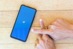 Loading logo of twitter with finger cross sign for anti fake news