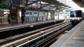 A Mo Chit bond BTS train enters Ratchathewi station. Bangkok, Thailand - August 14, 2018: A Mo Chit bond BTS train arrives at Ratchathewi station on August 14 stock video