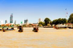 Day view of Chao Phraya River with boats and down-town buildings in Bangkok Royalty Free Stock Image