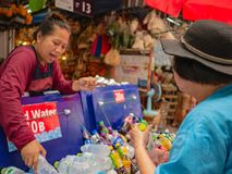 :unacquainted Seller selling the water of bottle to the tourist in Chatuchak Weekend Market bangkok thailand stock photos