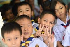 BANGKOK THAILAND - 23 Augustus, 2017: De groep Kleuterschoolkinderen of jonge studenten is gelukkige glimlach en houdt twee vinge Stock Afbeeldingen