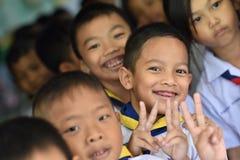 BANGKOK THAILAND - 23 Augustus, 2017: De groep Kleuterschoolkinderen of jonge studenten is gelukkige glimlach en houdt twee vinge Royalty-vrije Stock Fotografie