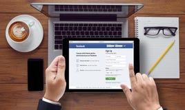 Bangkok, Thailand - breng 10, 2015 in de war: Mens op een ipad die Facebook doorbladeren Royalty-vrije Stock Fotografie