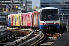 Bangkok, Thailand: BTS Skytrain. A Silom Line BTS Skytrain covered with painted advertising on each car approaching the Sala Daeng station in Bangkok, Thailand Stock Images