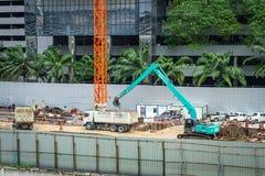 Bangkok - Thailand, 29 2018: Byggmästarearbetar- och grävskopapåfyllning royaltyfria foton