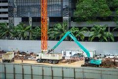 Bangkok - Thailand, 29 2018: Byggmästarearbetar- och grävskopapåfyllning arkivbild