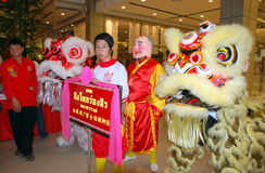 Bangkok, Thailand: Celebrating Chinese New Year. Laughing monk, sign bearer, and team of lion dancers waiting to go onstage to perform at the Central World Royalty Free Stock Images