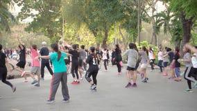 Bangkok, Thailand - circa Maart 2017: Aerobics in Lumpini-park Mensen die oefeningen doen openlucht stock video