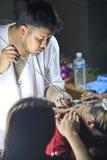BANGKOK, THAILAND - CIRCA MARCH 2013: Master makes traditional Yantra tattoo on magic tattoo Sak Yant holiday at Wat Bang Phra stock photo