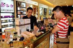Bangkok, Thailand: Customer Testing Fragrance. Customer testing a cologne fragrance at the Burberry counter in the upscale Central Chit Lom shopping center in Stock Images