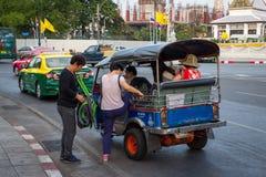 BANGKOK THAILAND DEC 12: Kinesiska turister är får upp på tuk-tuk Arkivbild