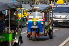 BANGKOK,THAILAND DEC 12: Tourists take tuk-tuk for convenience s. Ightseeing on DECEMBER 12, 2014 in Bangkok, Thailand Royalty Free Stock Photo