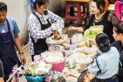 Street hawker cooking for papaya salad food for sale on the street. Green papaya salad is a spicy salad made from shredded unripe. Bangkok, Thailand - December stock photography
