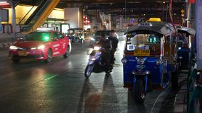 Bangkok, Thailand - 18 December, 2018: Traditional Thai taxi - Tuk Tuk awaits tourists along the road. Night traffic of stock video